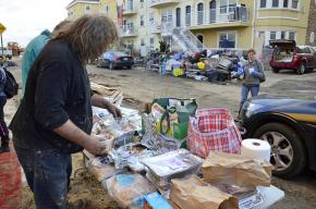 Residents in the Rockaways collect donated food items in a wreckage-strewn street